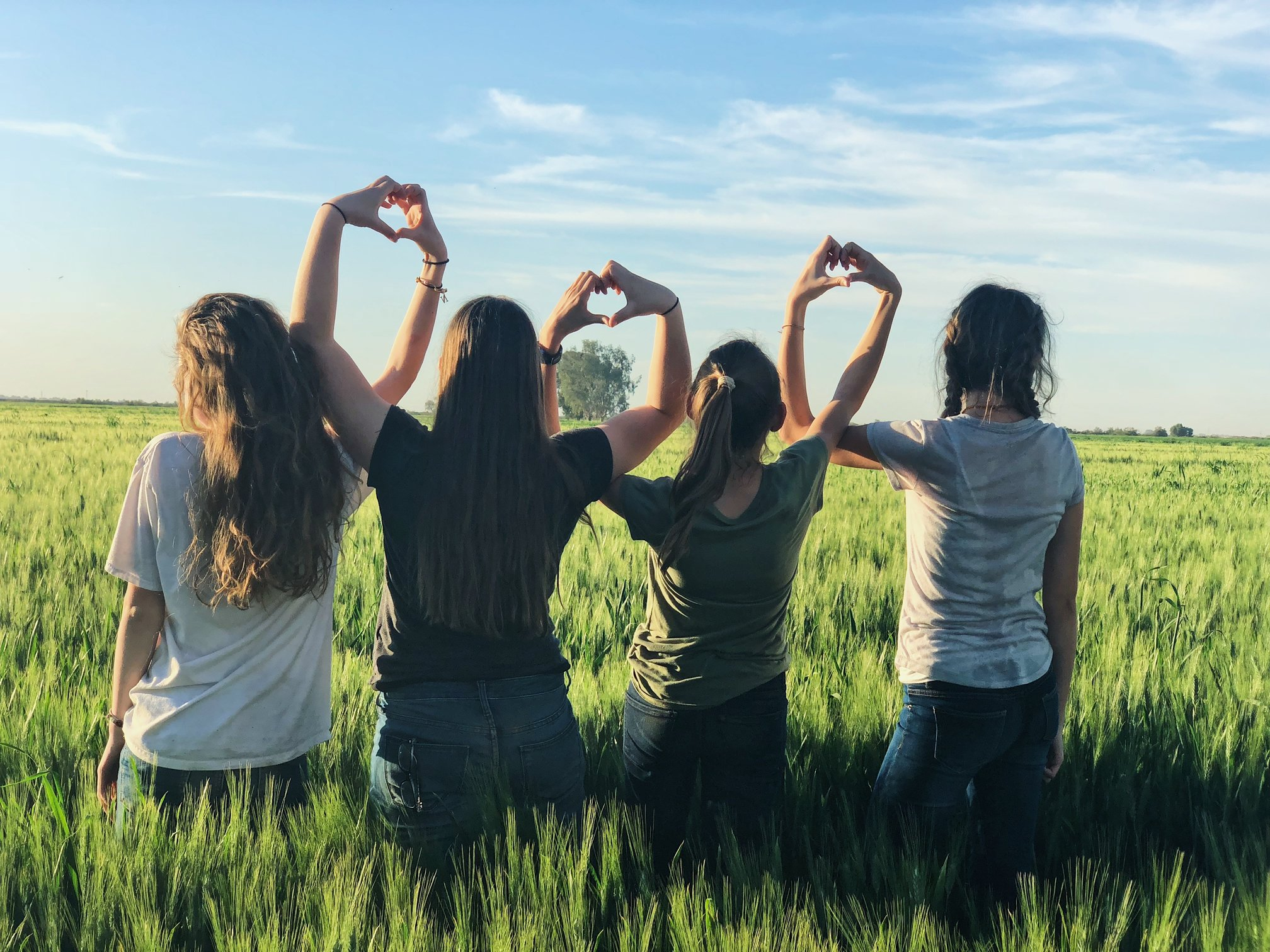 four women with hands in heart formation