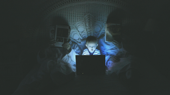 child in bed with blue light screen that is bad for sleep hygiene