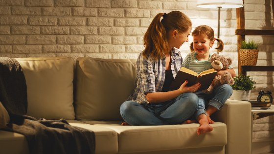 mom reading a book with her daughter before bedtime