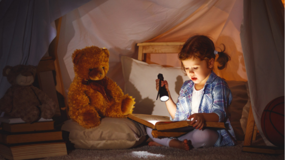 child reading with flashlight