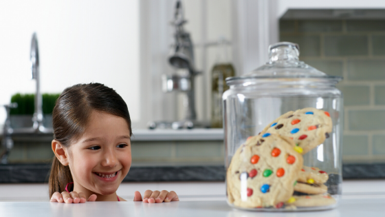 girl looking at a cookie jar for intuitive eating principle of saying yes