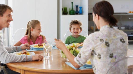 a family eating dinner together for intuitive eating principle of trusting their fullness and choices
