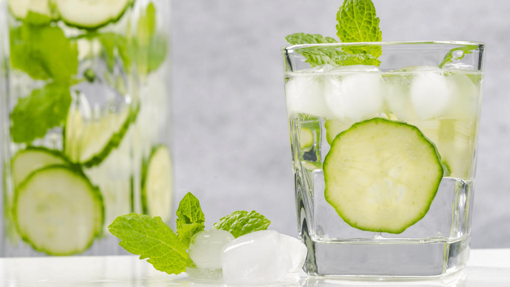 cucumber mint water in a glass with ice and cucumber slices