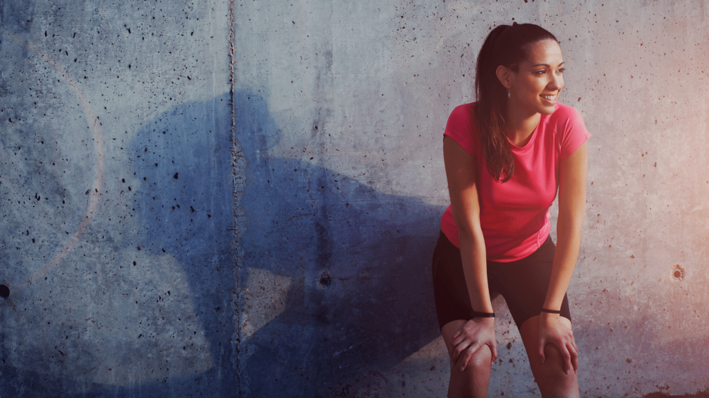 woman resting against wall and smiling after running