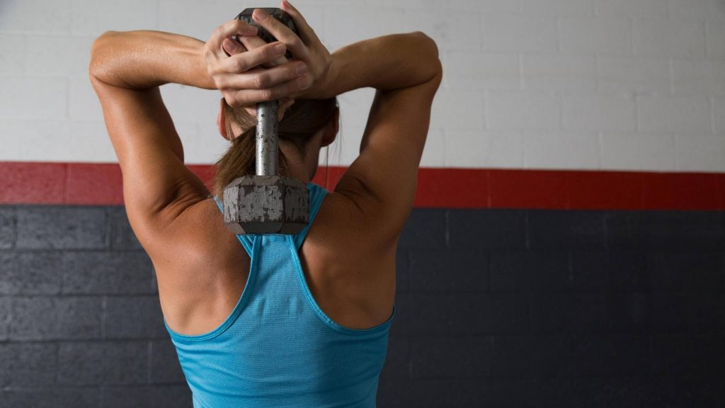 woman doing tricep exercise with dumbbell debunking does muscle burn fat