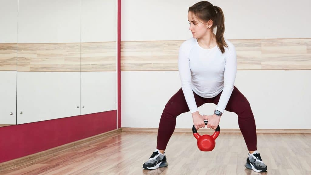 woman doing kettle bell exercise in front of gym mirror