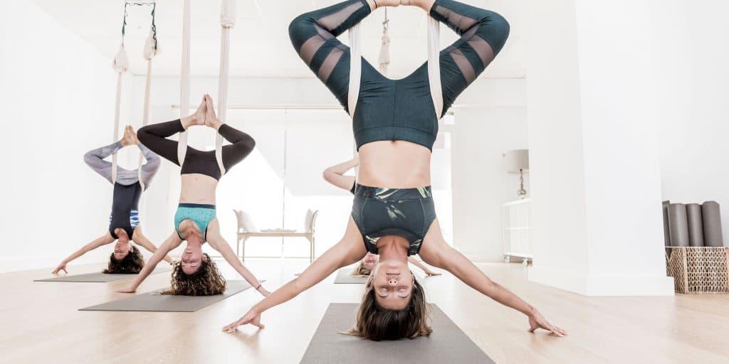 three women practicing aerial yoga